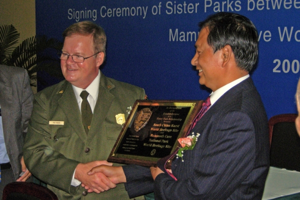 Mammoth Cave National Park Superintendent Patrick Reed (left) presents a commemorative plaque to Li Zhengping of Shilin Stone Forest, in honor of the signing of a Sister Park agreement Aug. 13 in Kunming, China.