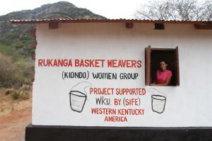 WKU SIFE student Amy Logan, who is coordinating sustainable economic development programs for WKU's cooperative Kenyan research program, stands in a new basket weaver's building constructed with funds returned to the local women from SIFE's previous basket initiatives.