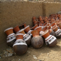 Dozens of colorful water storage pots near the outskirts of a village. These are for sale, but rarely seen in homes due to their high cost.