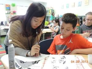 Ms. Wang Chunliu (Jasmine) teaches a student the proper calligraphy technique. (Photo by Tina Hargett)