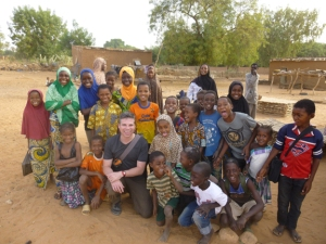 A group of Songhai women and children pose for a picture with WKU's Jonathan (Joneo) Oglesby after completing a group study in the remote village of Ganguel.