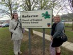 Harmony Hendrick and Jessica Roberts pose with the Harlaxton Primary School sign in Harlaxton, England.