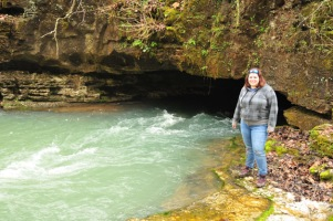 Kristen Coomer poses beside water flowing from a cave entrance at Greer Spring in southern Missouri.