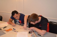 Balsa wood bridge construction during competition: Franklyn Perez and Tyler Baker.