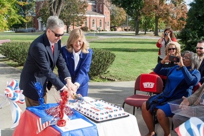 WKU Provost David Lee and Central Texas College Site Director Pamela Regester use a sword to cut a cake celebrating the signing of an articulation agreement between the two institutions.