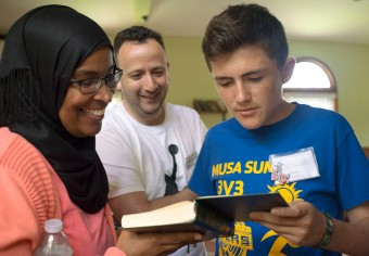 Berthed Nabaa-McKinney (left) of the Islamic Center of Nashville shows Hollis Maxson of Winston-Salem, N.C., passages in the Quran while Arabic teacher Lhousseine Guerwane watches during a field trip to the Islamic Center of Nashville as part of the Summer Program for Verbally and Mathematically Precocious Youth (VAMPY) in 2016. (Photo by Tucker Allen Covey)